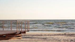 Una vista de la orilla de mar en un día ventoso en que las ondas vienen a la cubierta de madera empleada la playa metrajes
