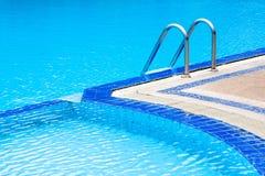 Una vista de la piscina azul clara ligera curvada con el ladde de acero Imagen de archivo