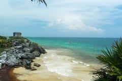 Una vista de la playa y del oc?ano debajo del templo de las ruinas mayas de dios del viento en Tulum fotografía de archivo libre de regalías