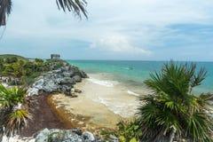 Una vista de la playa y del oc?ano debajo del templo de las ruinas mayas de dios del viento en Tulum imagen de archivo libre de regalías