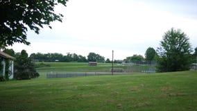 Una vista de larga distancia de un juego de béisbol de la bola o de la liga pequeña de la camiseta almacen de video