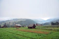 Una vista de las montañas cárpatas en la niebla, casas del pueblo Imagenes de archivo