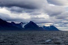 Una vista de las montañas de Svalbard con el sol que brilla de behing las nubes fotos de archivo libres de regalías