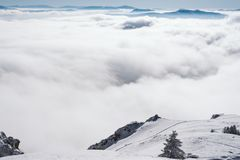 Una vista de los acantilados de la alta montaña en el valle cubierto con niebla imágenes de archivo libres de regalías