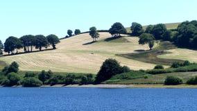 Una vista de los campos montañosos que miran a través del lago Wimbleball en Exmoor, Reino Unido fotos de archivo