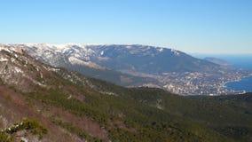 Una vista de los tops de montañas nevadas En el valle usted puede ver la ciudad de Yalta metrajes