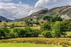 Una vista de montañas y de campos con las cabañas blancas foto de archivo