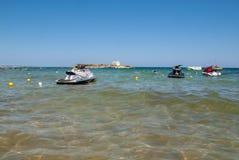 Una vista de una playa con las vespas de un agua en Malia Crete, Grecia fotografía de archivo libre de regalías