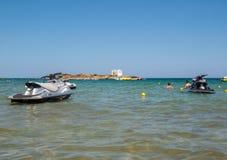Una vista de una playa con las vespas de un agua en Malia Crete, Grecia fotografía de archivo