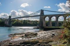 Una vista de puente colgante histórico de Menai que atraviesa el Mena Imagen de archivo