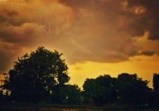Una vista de un cielo brillante de la puesta del sol detrás de los árboles imagen de archivo