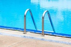 Una vista de una piscina azul clara ligera con la escalera de acero Fotos de archivo libres de regalías