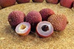 Una vista del corte transversal de una fruta del lichi con la semilla, al lado de las frutas enteras Para el postre foto de archivo libre de regalías