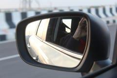 Una vista del espejo de la vista lateral del coche en una carretera imagen de archivo libre de regalías
