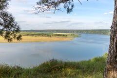 Una vista del fiume e del villaggio Cielo blu con le nubi Nel pino della priorità alta Fotografia Stock