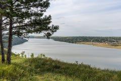 Una vista del fiume e del villaggio Cielo blu con le nubi Nel pino della priorità alta Fotografie Stock Libere da Diritti