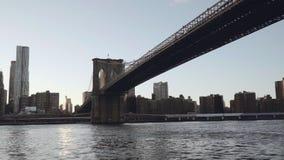 Una vista del horizonte del Lower Manhattan filmada del barco en el East River debajo del puente de Brooklyn en Nueva York, unida metrajes