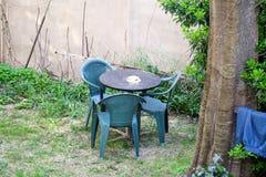 Una vista del jardín mediterráneo con muebles por un sistema de tres sillas verdes plásticas y de una tabla Los días de fiesta y  Foto de archivo libre de regalías