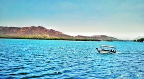 Una vista del lago con la barca si appanna l'acqua delle rocce immagini stock