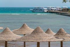 Una vista del Mar Rosso nell'Egitto con i picchi di vimini dagli ombrelli nella priorità alta Fotografia Stock