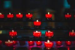 Una vista del primo piano di parecchie candele rosse accese ha un su un buio immagine stock libera da diritti