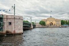 Una vista del puente de Dvortsovy y del edificio del Ministerio de marina de una barca que pasa rio abajo de Neva Fotografía de archivo libre de regalías