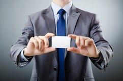Una vista delantera de un hombre de negocios que sostiene una tarjeta de visita Imagen de archivo