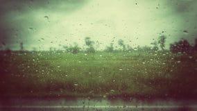 Una vista dell'annata del giacimento del riso dalla goccia di pioggia sulla finestra Fotografie Stock