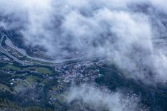 Una vista della città nella valle sopra le nuvole in alpi francesi Fotografia Stock