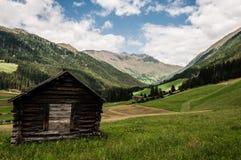 Una vista della valle alpina tipica con la capanna rustica Immagini Stock Libere da Diritti