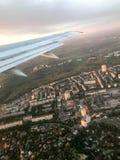 Una vista desde arriba de la ciudad con los edificios, las casas de la porta, las ventanas de los aviones en el ala con los motor foto de archivo libre de regalías