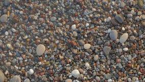 Una vista desde arriba de ondas, de la espuma y de piedras coloreadas Pebble Beach almacen de metraje de vídeo