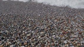 Una vista desde arriba de ondas, de la espuma y de piedras coloreadas Pebble Beach metrajes
