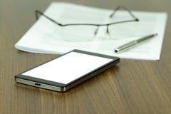 Una vista detallada de un escritorio del negocio con un teléfono móvil con un bl Imagen de archivo