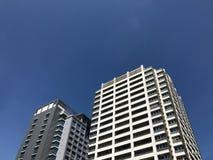 Una vista di angolo di due builgings moderni contro cielo blu Fotografia Stock