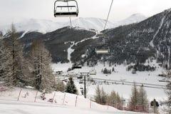 Una vista di bello villaggio stupefacente nel paesaggio e le montagne innevate e una cabina di funivia/ascensore nelle alpi Svizz Fotografia Stock Libera da Diritti
