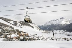 Una vista di bello villaggio stupefacente nel paesaggio e le montagne innevate e una cabina di funivia/ascensore nelle alpi Svizz Fotografia Stock