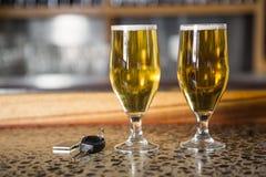 Una vista di due pinte delle chiavi dell'automobile e della birra Immagine Stock Libera da Diritti