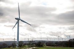 Una vista di panorama sopra il paesaggio del parco eolico in Germania con le turbine bianche del generatore Immagine Stock Libera da Diritti