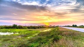 Una vista di tramonto con il paesaggio verde scenico alla strada della strada principale Fotografia Stock