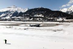 Una vista di un villaggio a St Moritz, paesaggio innevato e montagna, un aeroplano, una corsa con gli sci dell'uomo nelle alpi Sv Immagine Stock