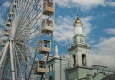 Una vista di vecchio campanile accanto alla ruota di ferris moderna, il quadrato del contratto, Kiev immagini stock libere da diritti