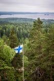 Una vista escénica de un lago y de un bosque del pino con la bandera finlandesa Fotos de archivo libres de regalías