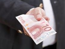 Una vista frontale della banconota dell'euro dieci in mano maschio Fotografia Stock Libera da Diritti