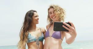 Una vista frontale di due amici femminili razza mista che prendono selfie con il telefono cellulare sulla spiaggia 4k video d archivio
