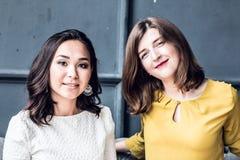 Una vista frontale di due giovani amici femminili sorridenti che si siedono nel salone a casa Immagini Stock