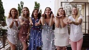 Una vista frontale di sei giovani donne caucasiche attraenti che soffiano allegro insieme i coriandoli colorati luminosi dalle lo video d archivio