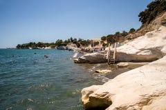 Una vista a la playa del ` s de los gobernadores con las sillas de cubierta y las sombrillas, Chipre Imagen de archivo