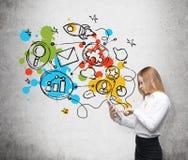 Una vista lateral de una mujer hermosa que está buscando algo en Internet, usando una tableta Los iconos coloridos se dibujan en  Fotos de archivo libres de regalías