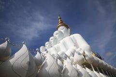 Una vista laterale di cinque statue bianche di Buddha che si siedono allineamento buono davanti a cielo blu Fotografia Stock Libera da Diritti